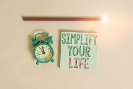 Word writing text Simplify Your Life. Business photo showcasing Manage your day work Take the easy way Organize Metal vintage alarm clock wakeup blank notepad marker colored background