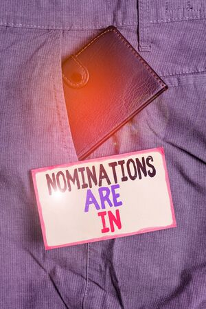 Conceptual hand writing showing Nominations Are In. Concept meaning Formally Choosing someone Official Candidate for an Award Small wallet inside trouser front pocket near notation paper Imagens