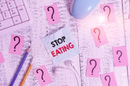 Writing note showing Stop Eating. Business concept for cease the activity of putting or taking food into the mouth Writing tools and scribbled paper on top of the wooden table Stock Photo