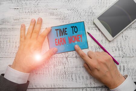 Writing note showing Time To Earn Money. Business concept for Get Paid for Work Done Invest on Business or Property Hand hold note paper near writing equipment and smartphone Stok Fotoğraf