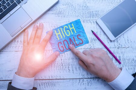 Conceptual hand writing showing High Goals. Concept meaning object of a demonstrating s is ambition or effort An aim or desired result Hand hold note paper near writing equipment and smartphone