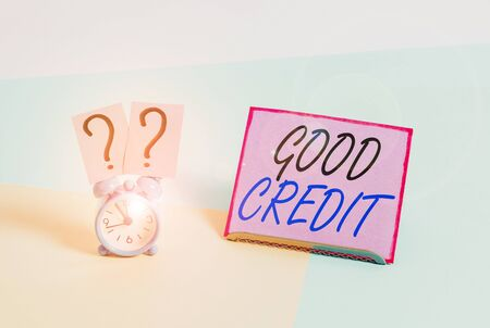 Word writing text Good Credit. Business photo showcasing borrower has a relatively high credit score and safe credit risk Mini size alarm clock beside a Paper sheet placed tilted on pastel backdrop Stok Fotoğraf