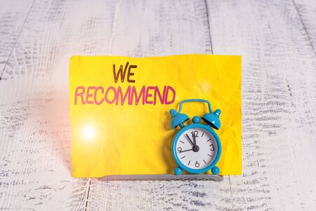 Word writing text We Recommend. Business photo showcasing suggest that someone or something would be good or suitable Mini blue alarm clock stand tilted above buffer wire in front of notepaper Stockfoto