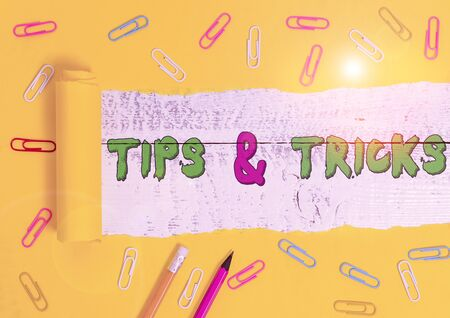 Word writing text Tips And Tricks. Business photo showcasing Steps Lifehacks Handy advice Recommendations Skills Stationary and torn cardboard placed above a wooden classic table backdrop