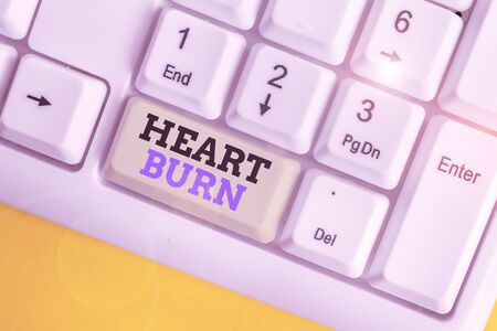 Conceptual hand writing showing Heart Burn. Concept meaning a burning sensation or pain in the throat from acid reflux White pc keyboard with note paper above the white background