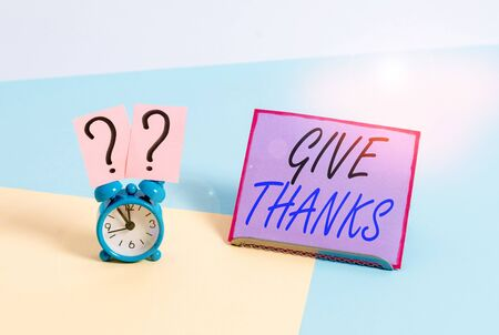 Word writing text Give Thanks. Business photo showcasing express gratitude or show appreciation Acknowledge the kindness Mini size alarm clock beside a Paper sheet placed tilted on pastel backdrop