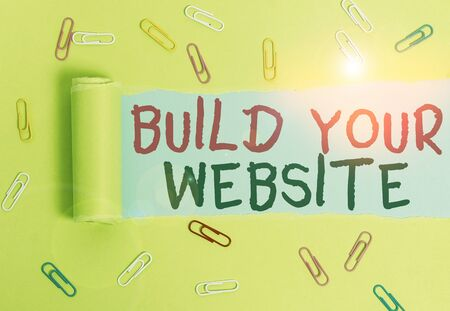 Writing note showing Build Your Website. Business concept for Setting up an ecommerce system to market a business Paper clip and torn cardboard on wood classic table backdrop