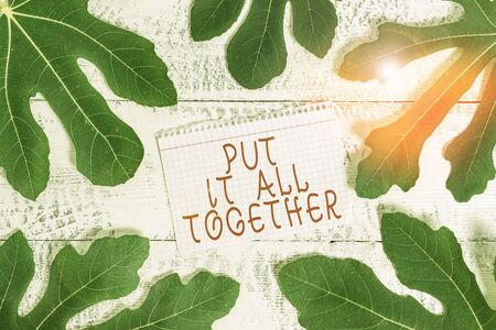 Word writing text Put It All Together. Business photo showcasing Join Collectively Unified Integrated Linked Merge Leaves surrounding notepaper above a classic wooden table as the background