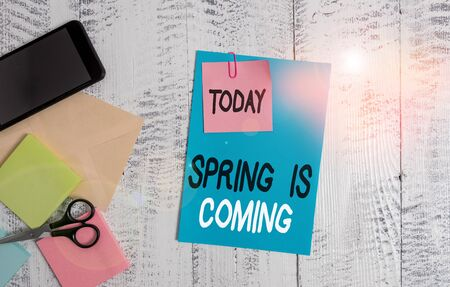 Writing note showing Spring Is Coming. Business concept for After winter season is approaching Enjoy nature flowers sun Envelope paper sheet smartphone notepads scissors wooden background