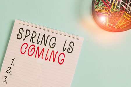 Writing note showing Spring Is Coming. Business concept for After winter season is approaching Enjoy nature flowers sun Blank empty notebook and stationary placed above pastel colour backdrop