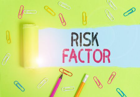 Word writing text Risk Factor. Business photo showcasing a condition behavior or other factor that increases danger Stationary and torn cardboard placed above a plain pastel table backdrop