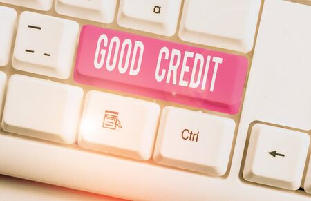 Writing note showing Good Credit. Business concept for borrower has a relatively high credit score and safe credit risk White pc keyboard with note paper above the white background