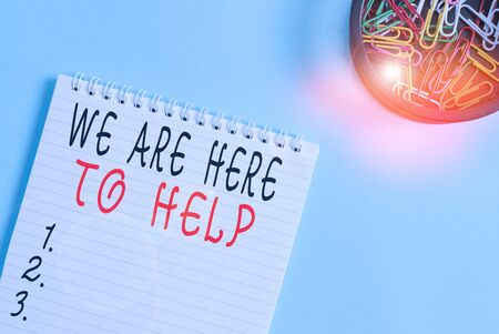 Writing note showing We Are Here To Help. Business concept for Someone who is always ready to Assist Support Give Blank empty notebook and stationary placed above pastel colour backdrop Stock fotó