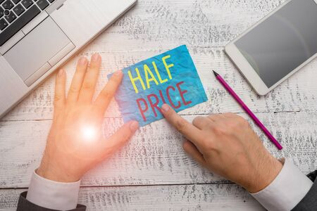 Conceptual hand writing showing Half Price. Concept meaning half the usual price at which something is offered for sale Hand hold note paper near writing equipment and smartphone