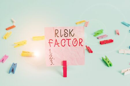 Handwriting text Risk Factor. Conceptual photo a condition behavior or other factor that increases danger Colored clothespin rectangle square shaped paper light blue background