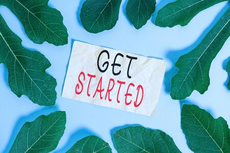 Conceptual hand writing showing Get Started. Concept meaning Begin an important period in one s is life or career Begin a task Leaves surrounding notepaper above empty soft pastel table