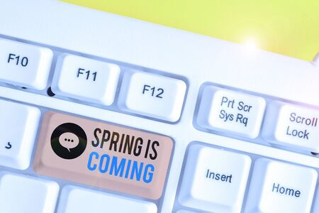 Conceptual hand writing showing Spring Is Coming. Concept meaning After winter season is approaching Enjoy nature flowers sun White pc keyboard with note paper above the white background Stock Photo