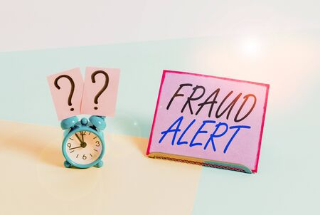 Word writing text Fraud Alert. Business photo showcasing security alert placed on credit card account for stolen identity Mini size alarm clock beside a Paper sheet placed tilted on pastel backdrop