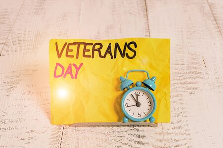 Word writing text Veterans Day. Business photo showcasing a public holiday to honour US veterans and victims of all wars Mini blue alarm clock stand tilted above buffer wire in front of notepaper