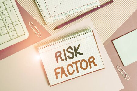 Writing note showing Risk Factor. Business concept for a condition behavior or other factor that increases danger Writing equipments and computer stuffs placed above colored plain table