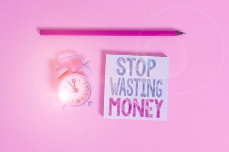 Word writing text Stop Wasting Money. Business photo showcasing Organizing Management Schedule lets do it Start Now Metal vintage alarm clock wakeup blank notepad marker colored background