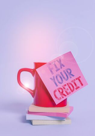 Conceptual hand writing showing Fix Your Credit. Concept meaning Keep balances low on credit cards and other credit Coffee cup colored sticky note stacked pads plain background