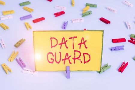 Word writing text Data Guard. Business photo showcasing analysisage databases to survive disasters and data corruptions Colored clothespin papers empty reminder blue floor background office pin