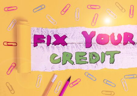 Word writing text Fix Your Credit. Business photo showcasing Keep balances low on credit cards and other credit Stationary and torn cardboard placed above a wooden classic table backdrop
