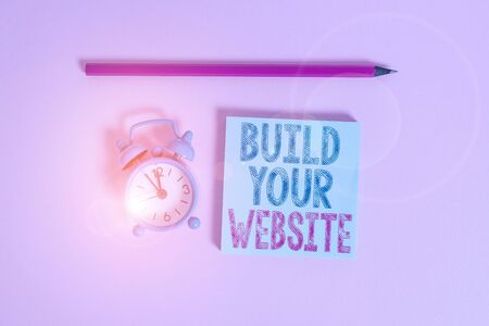 Word writing text Build Your Website. Business photo showcasing Setting up an ecommerce system to market a business Metal vintage alarm clock wakeup blank notepad marker colored background