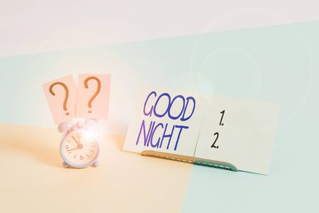 Writing note showing Good Night. Business concept for expressing good wishes on parting at night or before going to bed Alarm clock beside a Paper sheet placed on pastel backdrop