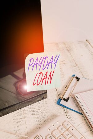 Conceptual hand writing showing Payday Loan. Concept meaning Something lent or furnished on condition being returned Note paper taped to black screen near keyboard stationary