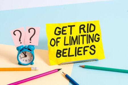 Text sign showing Get Rid Of Limiting Beliefs. Business photo text remove negative beliefs and think positively Mini size alarm clock beside stationary placed tilted on pastel backdrop