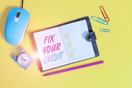 Word writing text Fix Your Credit. Business photo showcasing Keep balances low on credit cards and other credit Locked diary sheets clips marker mouse alarm clock colored background