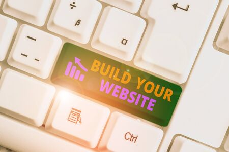 Writing note showing Build Your Website. Business concept for Setting up an ecommerce system to market a business White pc keyboard with note paper above the white background
