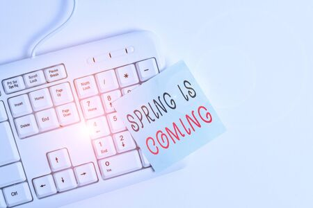 Writing note showing Spring Is Coming. Business concept for After winter season is approaching Enjoy nature flowers sun White pc keyboard with empty note paper above white background