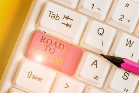 Conceptual hand writing showing Road To Success. Concept meaning studying really hard Improve yourself to reach dreams wishes White pc keyboard with note paper above the white background