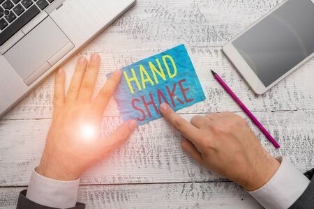 Conceptual hand writing showing Hand Shake. Concept meaning an act showing that you have made an agreement or greeting Hand hold note paper near writing equipment and smartphone