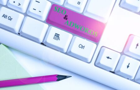 Writing note showing Seo And Adwords. Business concept for Pay per click Digital marketing adsense White pc keyboard with note paper above the white background Banco de Imagens