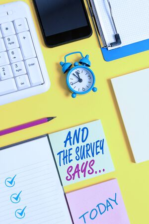 Writing note showing And The Survey Says. Business concept for doing poll and bring the results discuss with others White paper with copy space with paper clips clock and pc keyboard