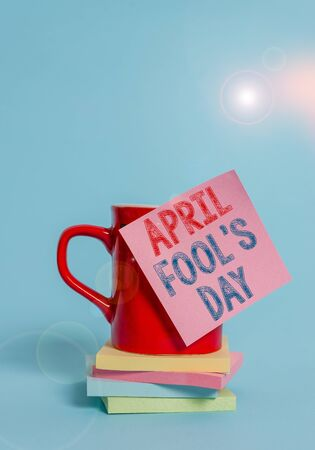 Conceptual hand writing showing April Fool S Day. Concept meaning Practical jokes humor pranks Celebration funny foolish Coffee cup colored sticky note stacked pads plain background