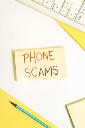 Text sign showing Phone Scams. Business photo showcasing use of telecommunications for illegally acquiring money Flat lay above table with pc keyboard and copy space paper for text messages Stock Photo