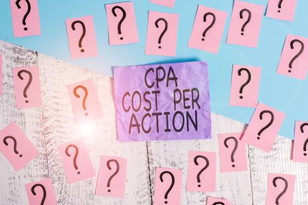 Text sign showing Cpa Cost Per Action. Business photo showcasing Commission paid when user Clicks on an Affiliate Link Scribbled and crumbling papers with thick cardboard above wooden table
