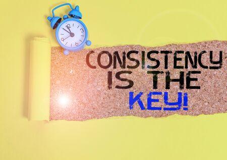 Escritura de texto escrito, la consistencia es la clave. Foto conceptual rompiendo malos hábitos y formando buenos Despertador y cartón roto colocado sobre un fondo de mesa clásico de madera Foto de archivo
