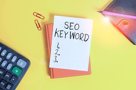 Text sign showing Seo Keyword. Business photo showcasing phrases in your web content that help showing find your site Pile of empty papers with copy space on the table
