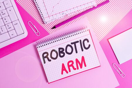 Writing note showing Robotic Arm. Business concept for programmable mechanical arm with similar function of a huanalysis arm Writing equipments and computer stuffs placed above colored plain table 写真素材