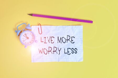 Conceptual hand writing showing Live More Worry Less. Concept meaning Have a good attitude motivation be careless enjoy life Metal alarm clock ccrushed sheet pencil colored background