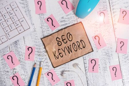 Conceptual hand writing showing Seo Keyword. Concept meaning phrases in your web content that help showing find your site Writing tools and scribbled paper on top of the wooden table