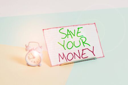 Handwriting text writing Save Your Money. Conceptual photo keep your savings in bank or stock to protect it Dont waste Mini size alarm clock beside a Paper sheet placed tilted on pastel backdrop Stok Fotoğraf