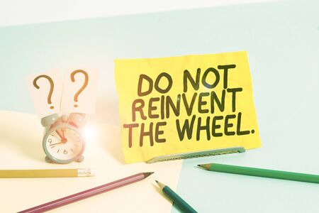 Text sign showing Do Not Reinvent The Wheel. Business photo text stop duplicating a basic method previously done Mini size alarm clock beside stationary placed tilted on pastel backdrop