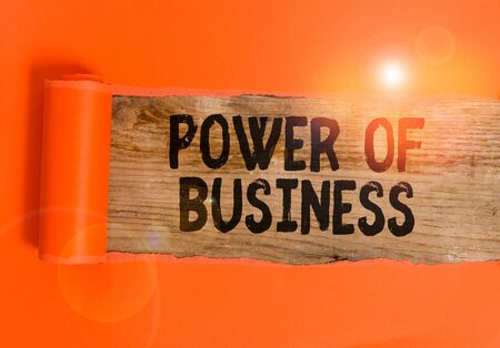 Word writing text Power Of Business. Business photo showcasing The ability to influence peers for attaining the goals Cardboard which is torn in the middle placed above a wooden classic table